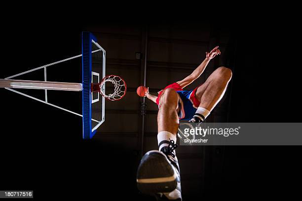 below view of a basketball player slam dunking the ball. - basketball shoe stock photos and pictures