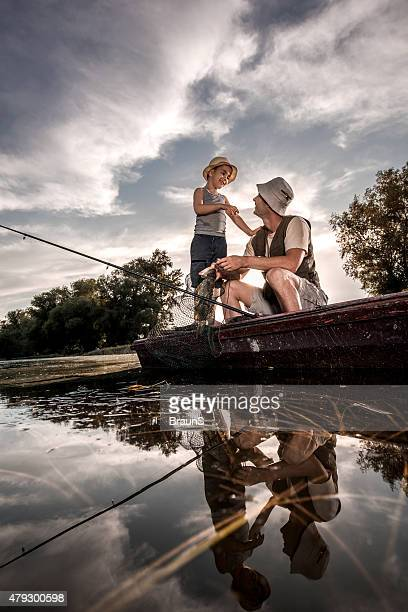 Below view of a father and son communicating during fishing.