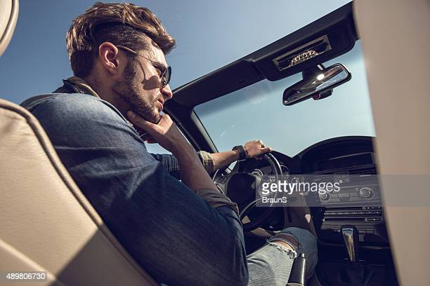 Below view of a pensive man driving a convertible car.