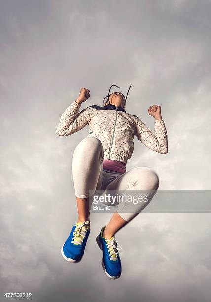 Below view of a woman jumping against moody sky.