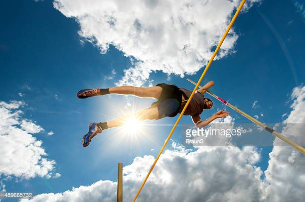 Below view of a young athlete at pole vault competition.