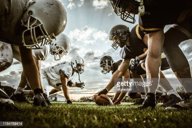 below view of american football players on a beginning of the match. - match sportivo foto e immagini stock