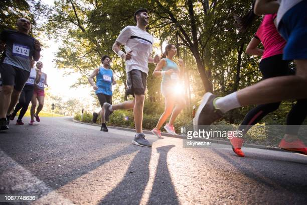 below view of athletes running a marathon on a road in nature. - marathon stock pictures, royalty-free photos & images