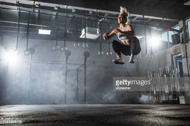 below view of athletic woman exercising jumps in a gym. - high up stock pictures, royalty-free photos & images