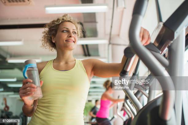 Below view of athletic woman with water bottle in gym.
