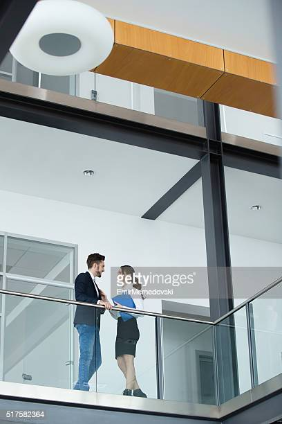 below view of business couple flirting in a hallway. - emir memedovski stock pictures, royalty-free photos & images