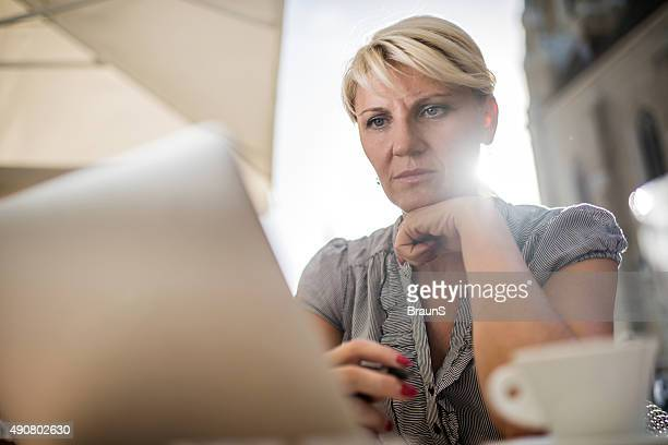 Below view of businesswoman working on computer in a cafe.
