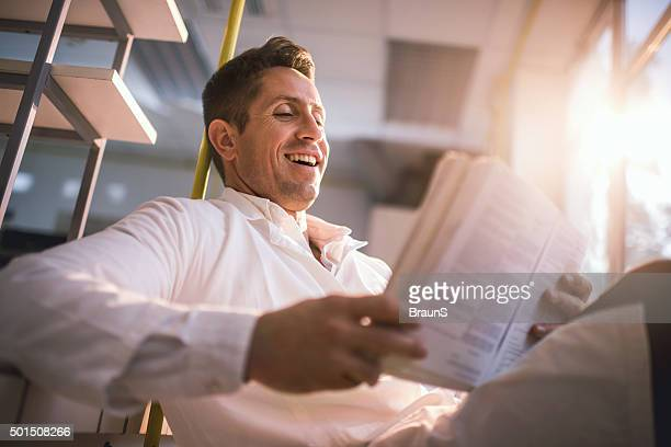 Below view of cheerful doctor reading medical data.
