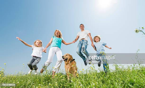 Below view of cheerful family jumping in a meadow.