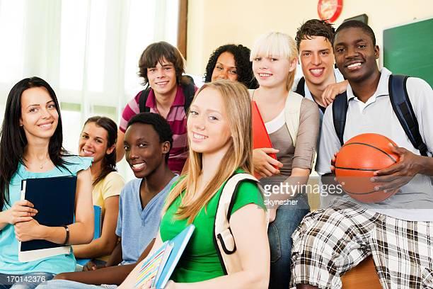 Au-dessous de vue de joyeux étudiants à la recherche dans la caméra.