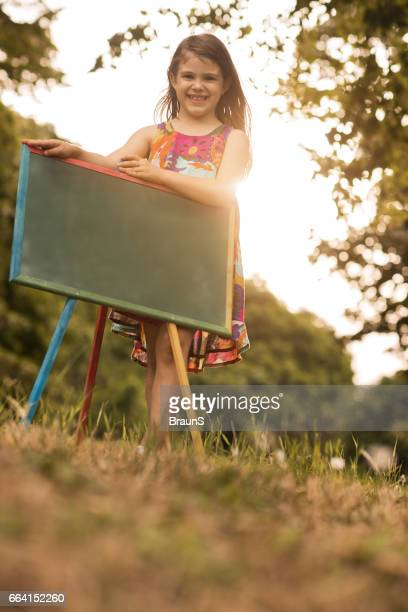 Below view of cute girl with blackboard in nature.