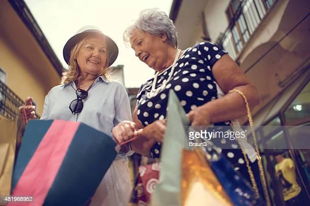 Below view of elderly women looking inside of shopping bags.
