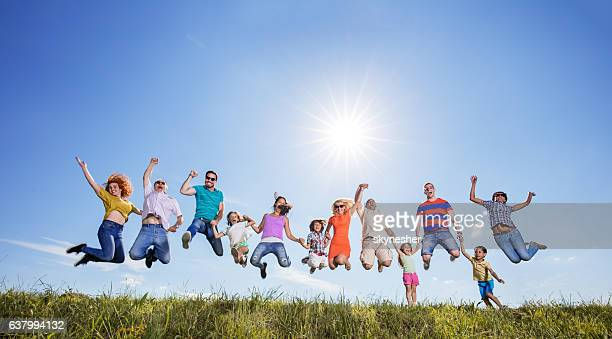 Below view of excited people jumping against the sky.