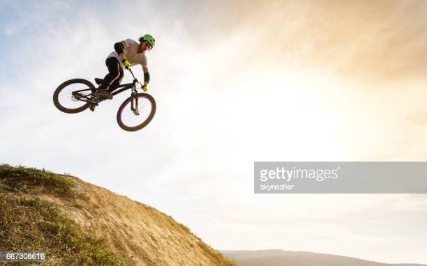 Below view of extreme cyclist jumping against the sky.