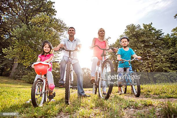 Below view of family riding bikes in the park.