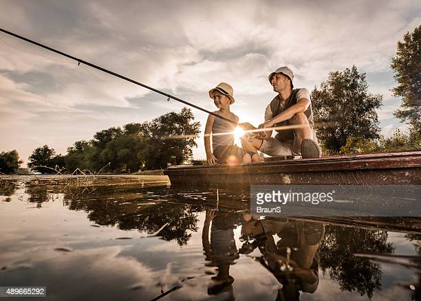 Below view of father and son in fishing at sunset.