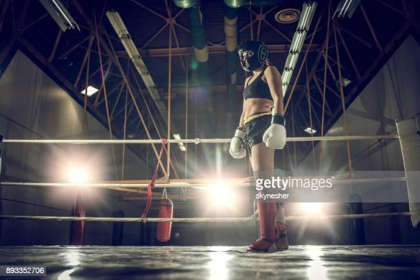 Ci-dessous la vue du joueur de kick-boxing féminin debout dans un anneau.