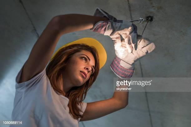 Below view of female manual worker repairing light in renovating apartment.