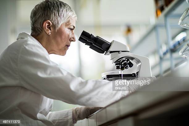 Below view of female scientist looking through a microscope.