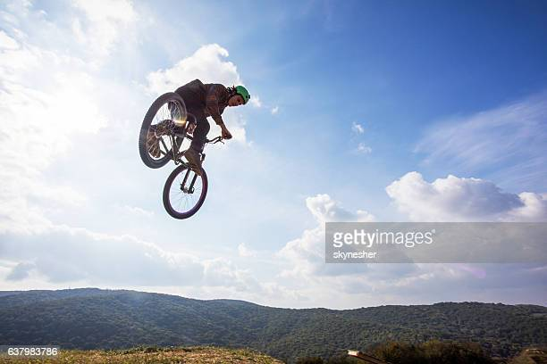 Below view of freestyle cyclist performing motowhip against the sky.