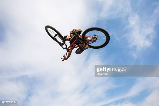 Below view of freestyle cyclist performing tabletop against the sky.