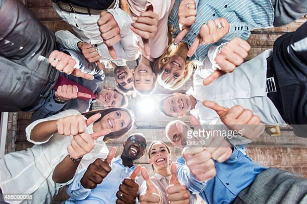 Debajo de vista del grupo de gente de negocios mostrando pulgar hacia arriba.