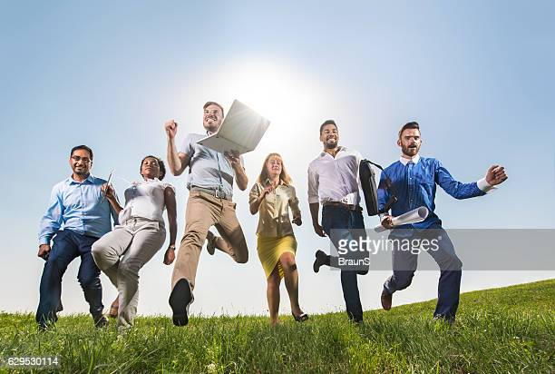 Below view of group of happy business people running outdoors.