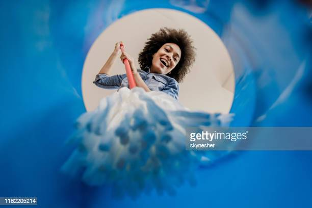 below view of happy black woman dipping the mop into the bucket. - daily bucket stock pictures, royalty-free photos & images