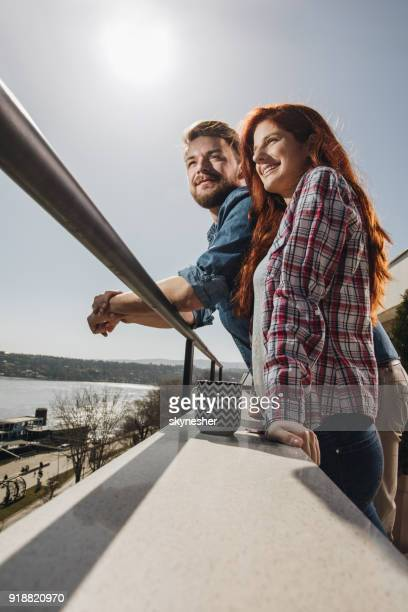 below view of happy couple enjoying in view from their terrace. - women of penthouse stock photos and pictures
