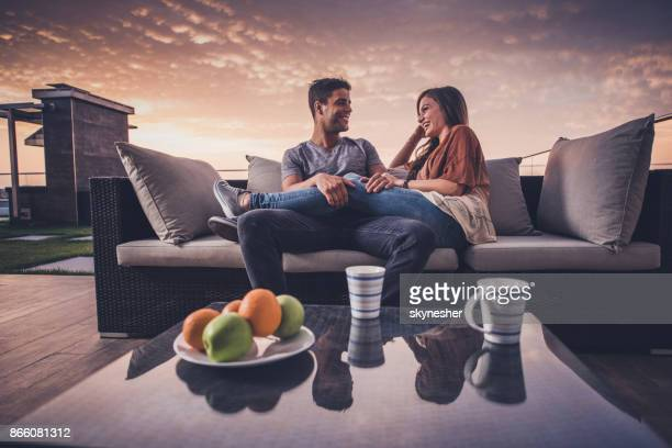 Below view of happy couple enjoying on a penthouse patio at sunrise.