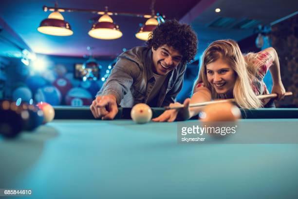 幸せなカップルのプールのホールでビリヤードのビューの下