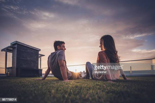 Below view of happy couple relaxing on grass at sunrise and communicating.
