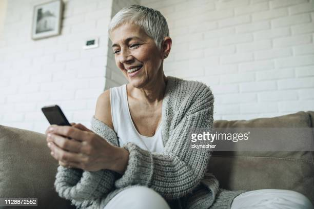 below view of happy mature woman text messaging on mobile phone. - candid forum stock pictures, royalty-free photos & images