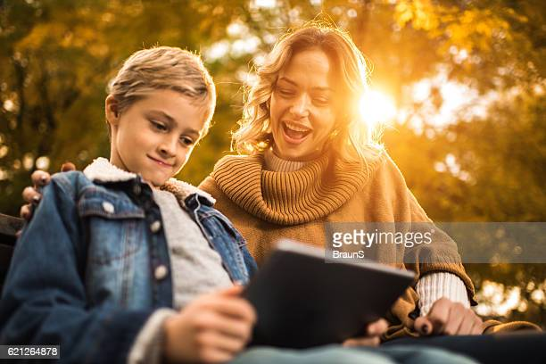 Below view of happy mother and son using touchpad outdoors.