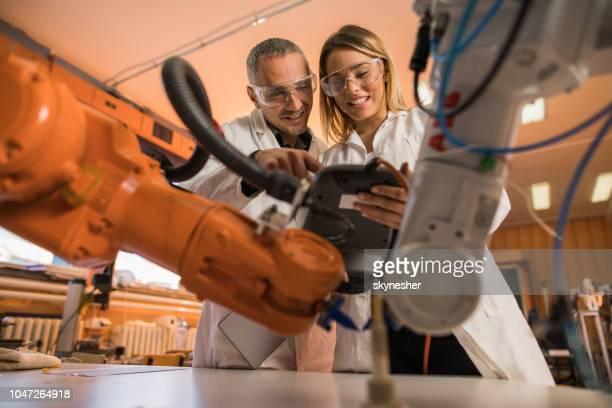 abaixo vista do cientista feliz cooperando enquanto trabalhava no braço robótico em laboratório. - robô - fotografias e filmes do acervo