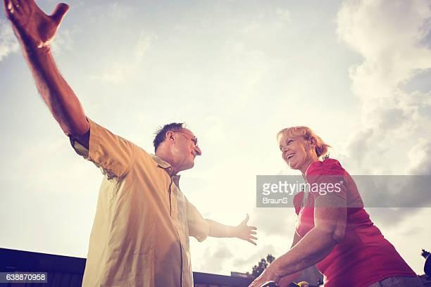 Below view of happy senor people greeting against the sky.
