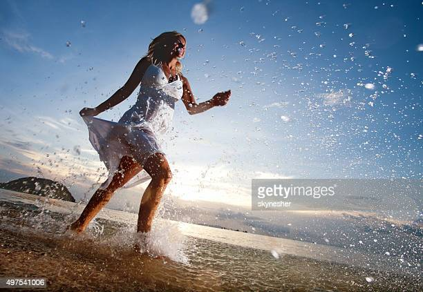 Below view of happy woman running on the beach.