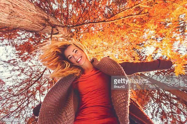 Abaixo vista de feliz Jovem mulher a divertir-se no Outono.