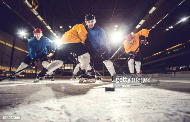 below view of ice hockey players having a match in a rink. - ice hockey stick stock pictures, royalty-free photos & images