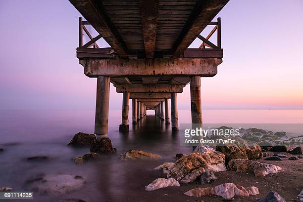 Below View Of Jetty In Sea Against Sky During Sunset