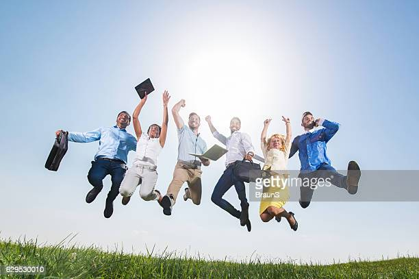 Below view of large business team jumping of joy outdoors.