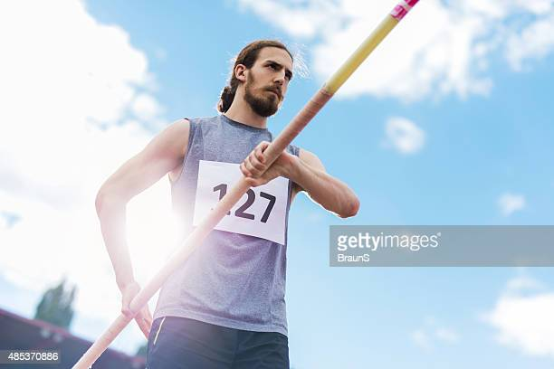 Below view of male athlete preparing for a pole vault.