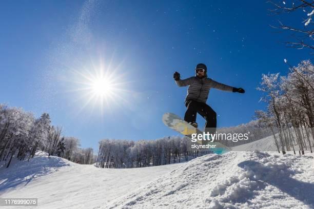 ci-dessous la vue du snowboarder masculin faisant des tours sur la neige. - montenegro photos et images de collection