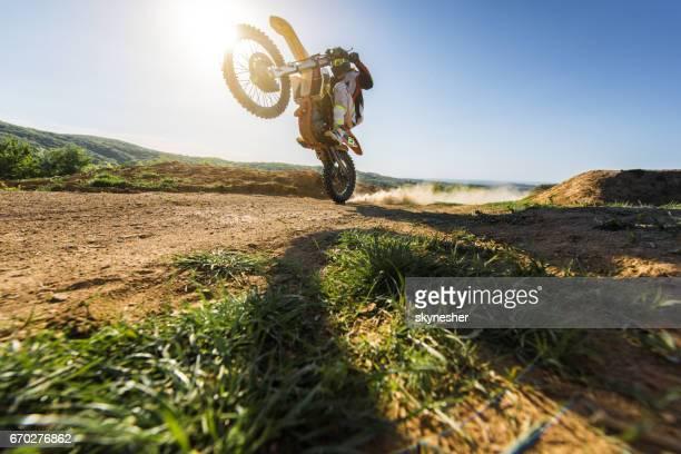 Unter Ansicht des Motocross Biker Balanceakt am Hinterrad.