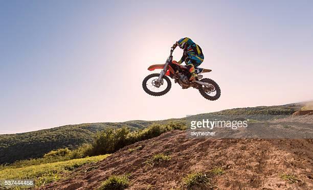 Unten Blick auf Motorradfahrer, die Durchführung Hochsprung gegen den Himmel.