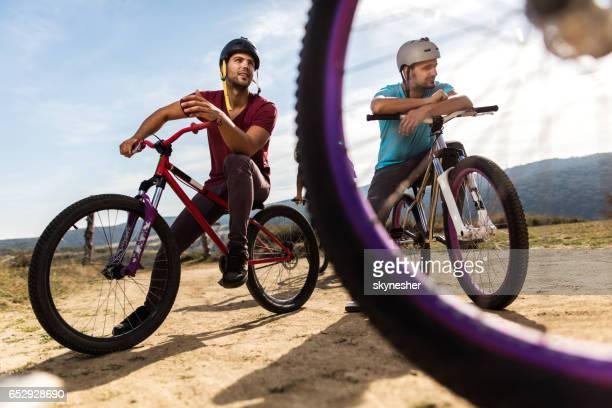 below view of mountain bike cyclists relaxing on dirt road. - bicycle trail outdoor sports stock photos and pictures