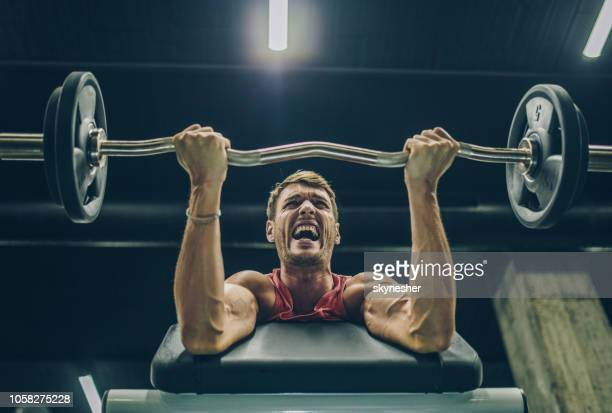below view of muscular build man making an effort while exercising with barbell. - sportsperson stock pictures, royalty-free photos & images