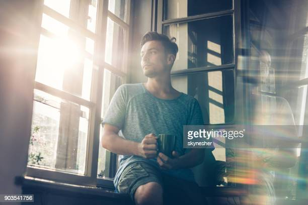 Below view of pensive man with coffee cup by the window.