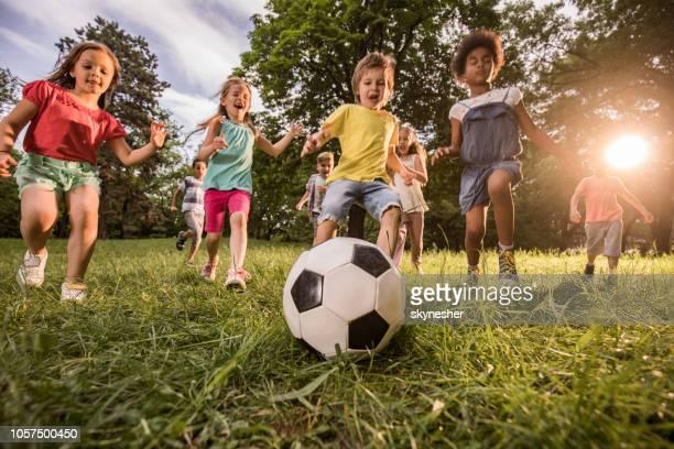 below view of playful children having fun while playing soccer in nature. - somente crianças imagens e fotografias de stock