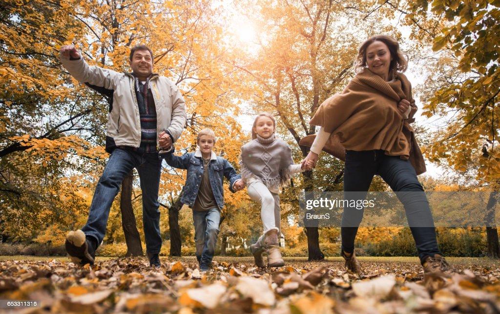 Onder zicht op speelse familie tijdens herfstdag. : Stockfoto